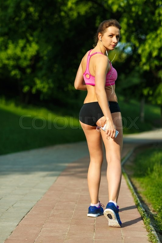 Stock image of 'Young sporty woman resting while jogging in the park'