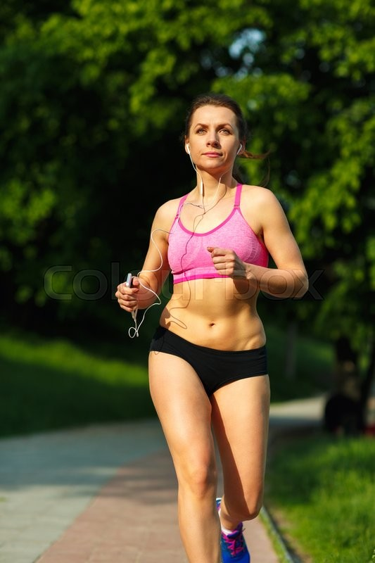 Stock image of 'Young fitness woman runner running on trail in the morning'