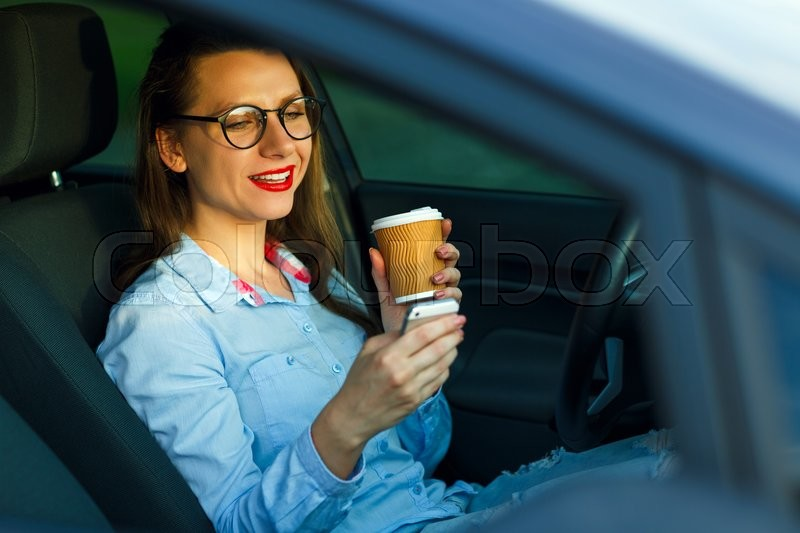 Stock image of 'Young businesswoman sending a text message and drinking coffee while driving a car'