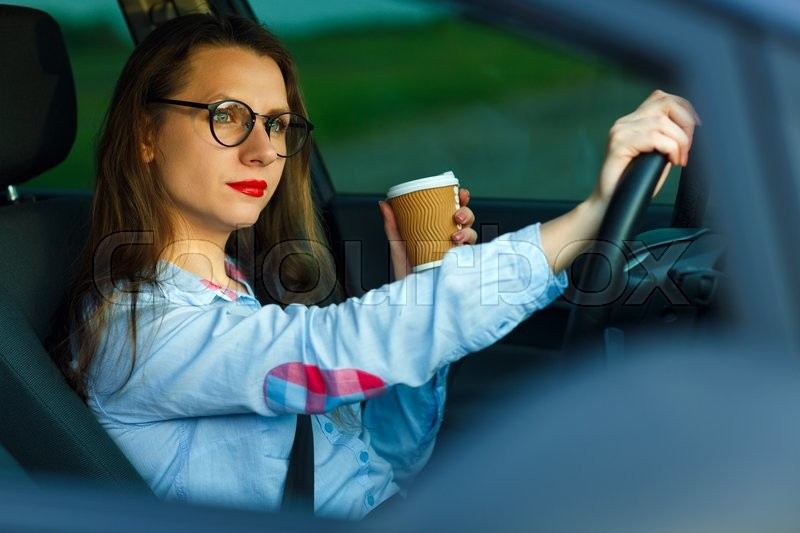 Stock image of 'Happy young woman with coffee to go driving her car'