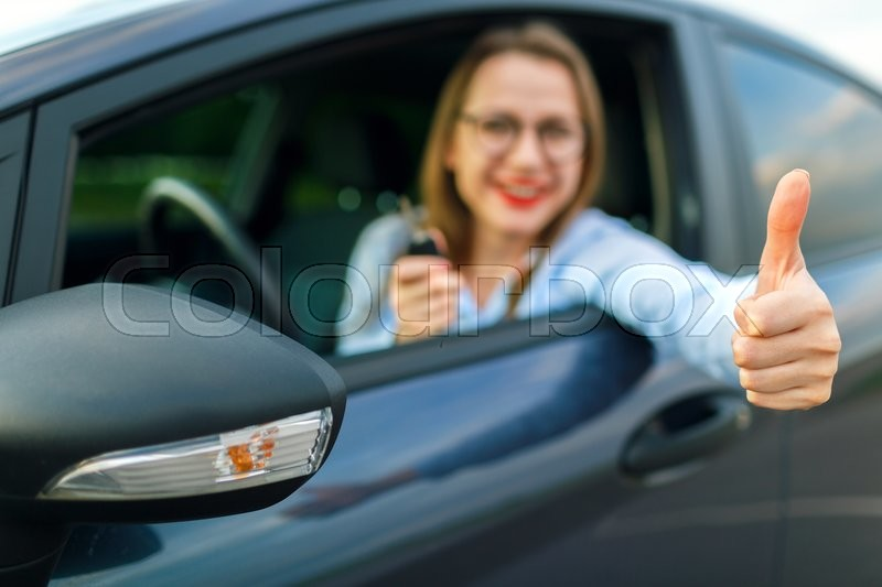 Stock image of 'Young happy woman sitting in a car with the keys in her hand and thumb up - concept of buying a used car or a rental car'