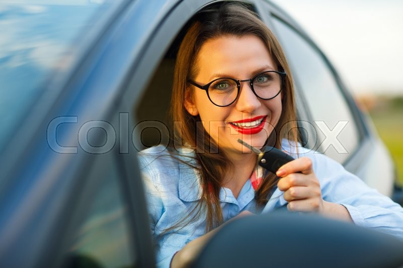 Stock image of 'Young pretty woman sitting in a car with the keys in hand - concept of buying a used car or a rental car'