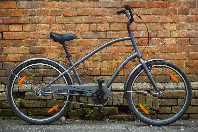 Stock image of 'Black retro vintage bicycle with old brick wall'