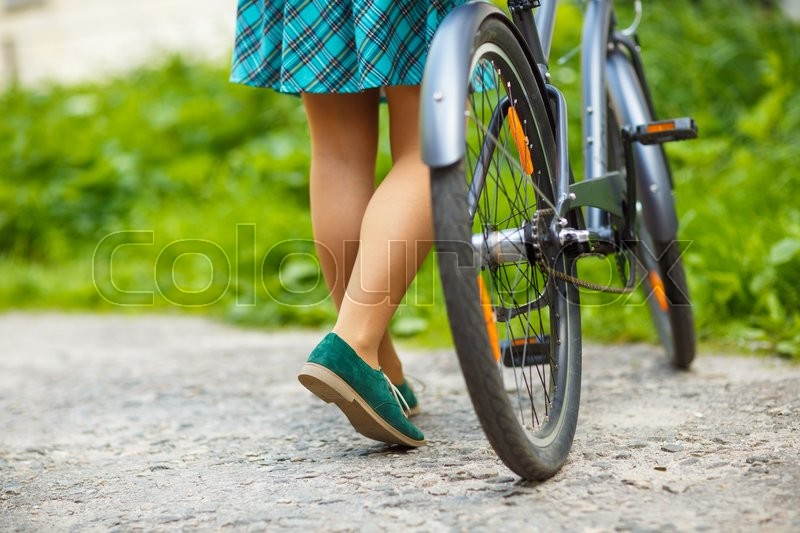 Stock image of 'Legs of a woman in shoes with a bicycle close up'