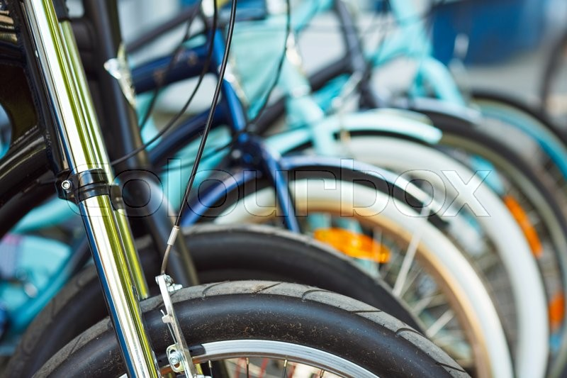 Stock image of 'Close up of wheel detail of a group of bicycles on parking'