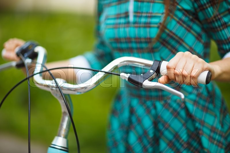 Stock image of 'Girl in green dress walking with her bicycle outdoors'