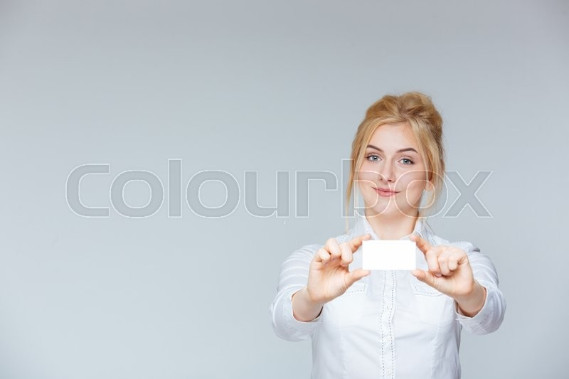 Stock image of 'Happy attractive young businesswoman showing blank business card'