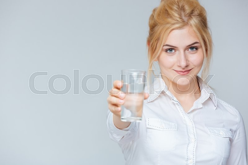 Stock image of 'Smiling cute young businesswoman giving you a glass of water'