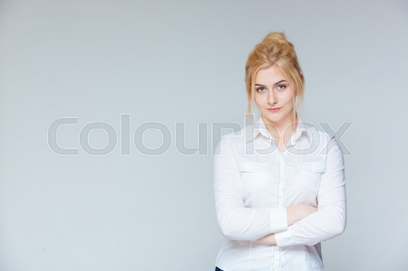 Stock image of 'Serious pretty young businesswoman standing with arms crossed'