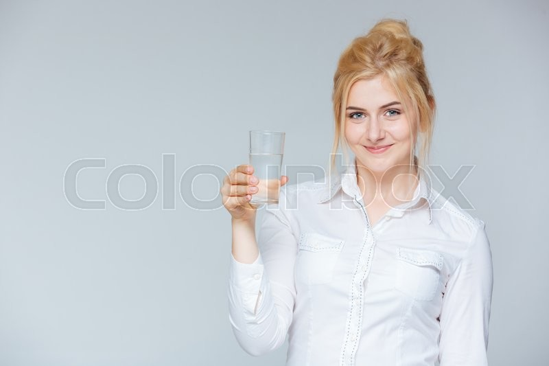 Stock image of 'Happy lovely young businesswoman holding glass of water'