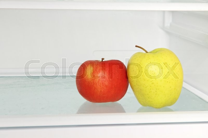 Stock image of 'Yellow and red apple in domestic refrigerator taken closeup.Healthy lifestyle.'