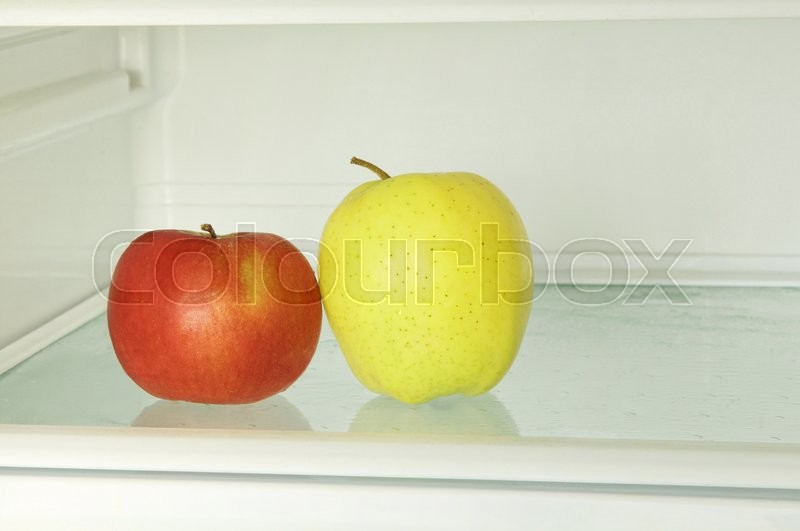 Stock image of 'Healthy lifestyle.Red and yellow apple in domestic refrigerator taken closeup. Toned image.'