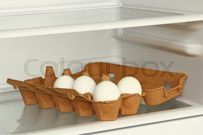 Stock image of 'Eggs in a paper box on refrigerator shelf taken closeup.'
