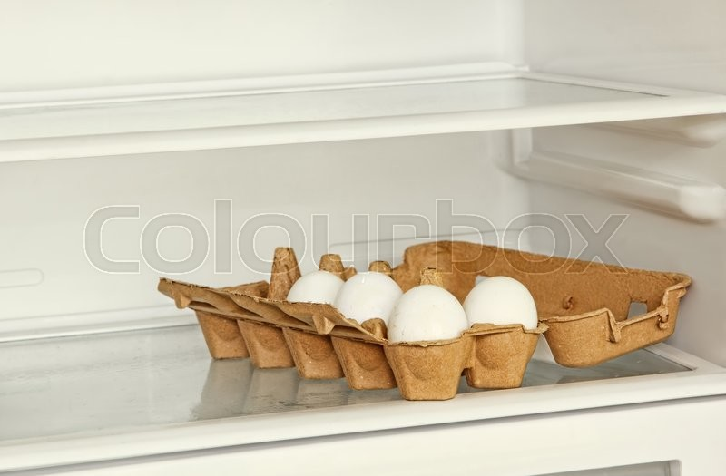 Stock image of 'Fresh eggs in a paper box on refrigerator shelf taken closeup.'