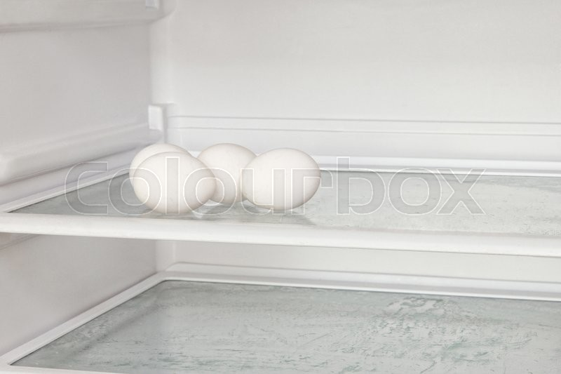 Stock image of 'Fresh chicken eggs on refrigerator shelf taken closeup.'