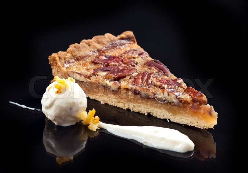 Stock image of 'pecan pie slice with ice cream ball on black background'