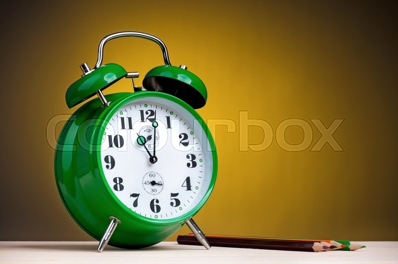 Stock image of 'Green alarm clock with pencils on table'