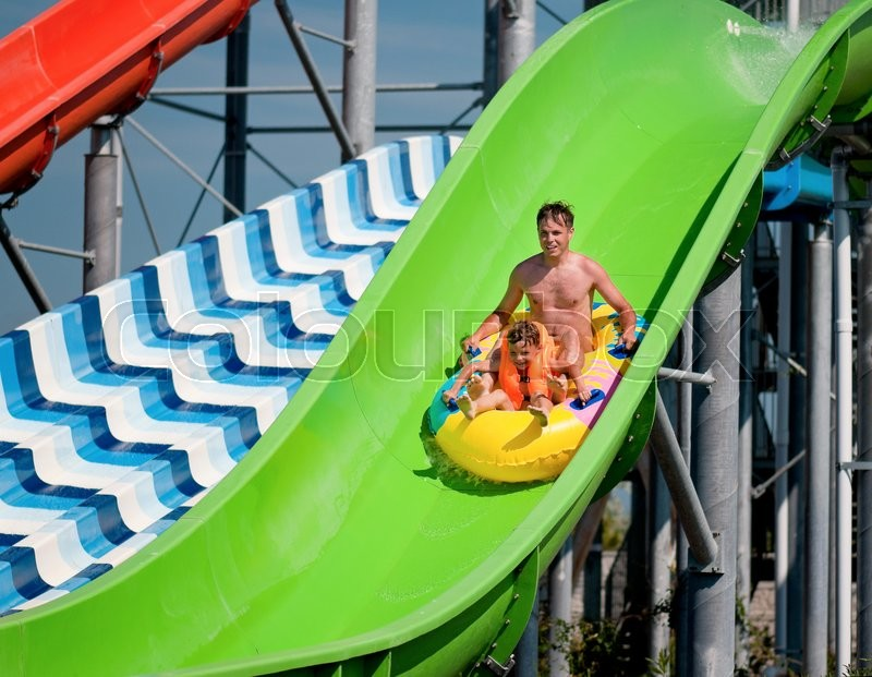 Stock image of 'Happy family - father with son - having fun water sliding at aqua park'