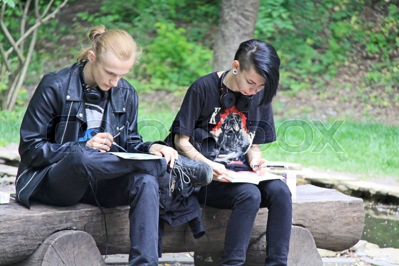 Stock image of 'Student pair studying together in park'