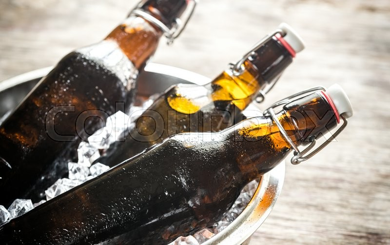 Stock image of 'Bottles of beer in ice cubes'