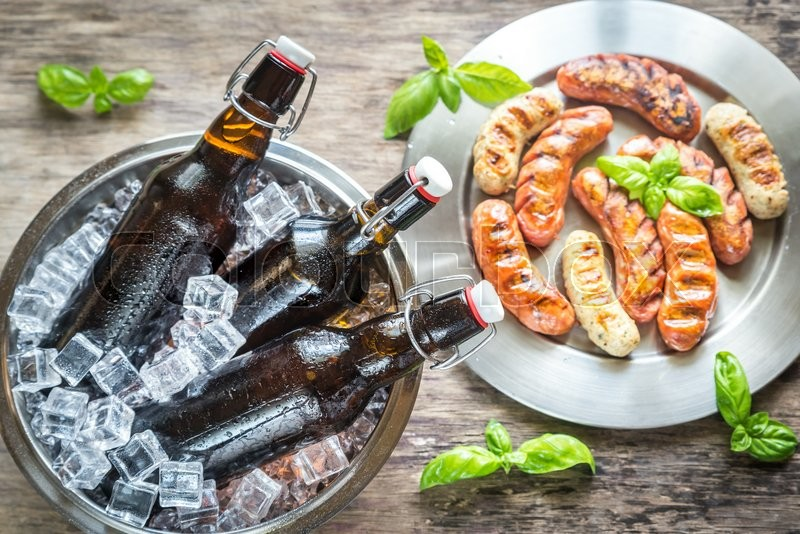 Stock image of 'Grilled sausages with bottles of beer'