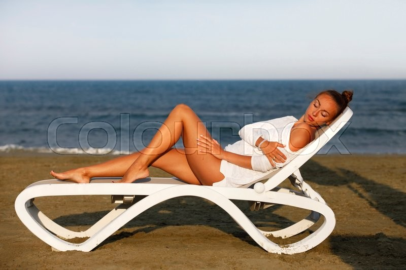 Stock image of 'Beautiful girl on a deckchair on the coastline'