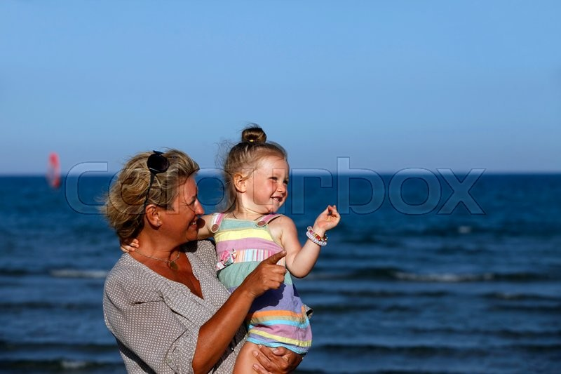 Stock image of 'Grandmother with a little granddaughter on the beach'