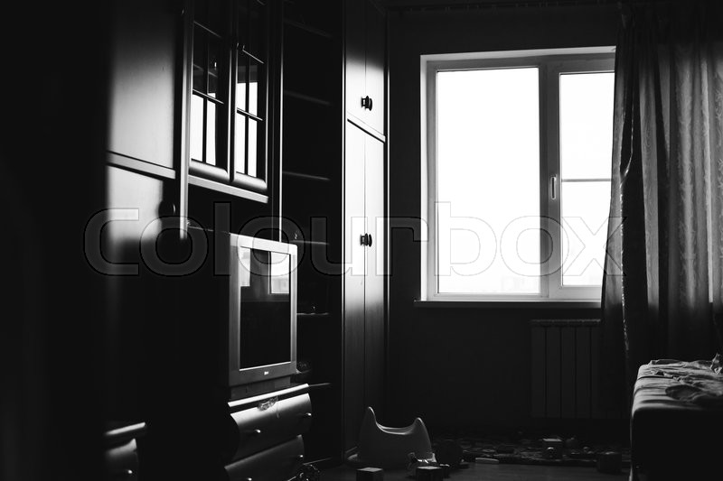 Stock image of 'fragment of a living room with a large window, a TV, wardrobe and children's toys in black and white'
