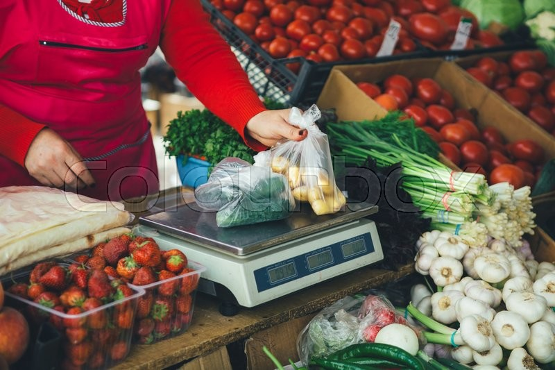 Stock image of 'the seller is weighing vegetables on scales on the market summer day'
