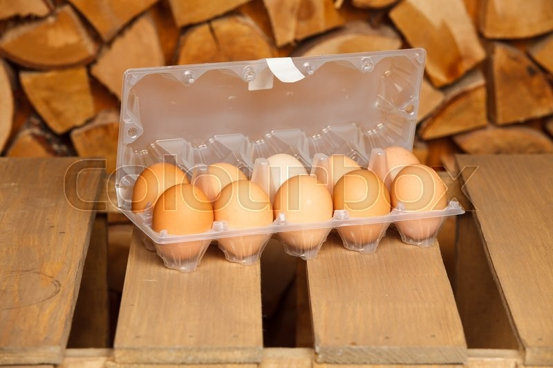 Stock image of 'Dozen of brown eggs on brown wooden stand'