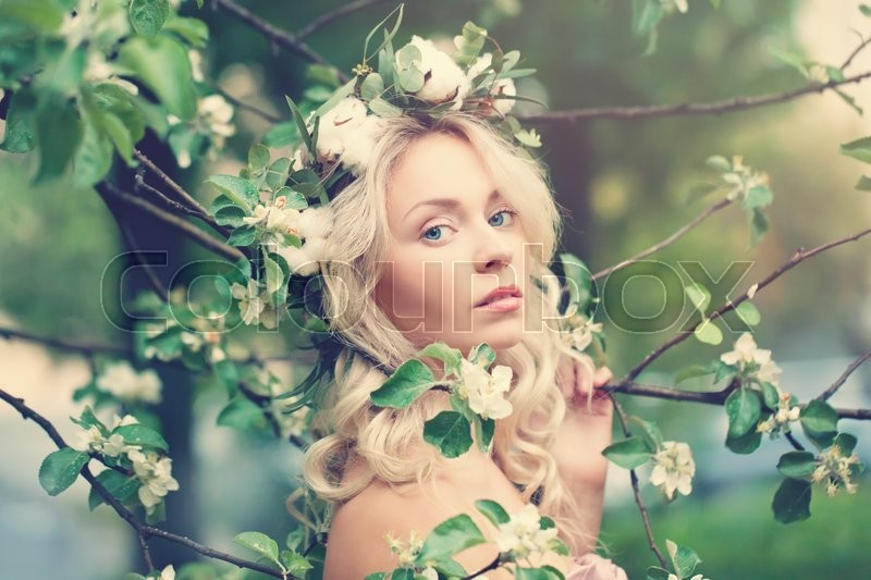 Stock image of 'Beautiful Woman with Blonde Hair on Spring Blossom Background'