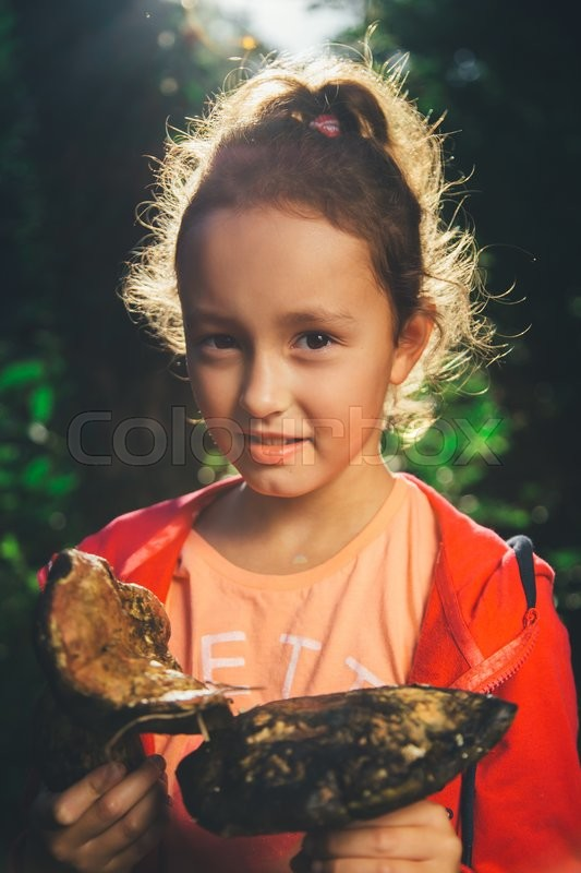 Stock image of 'girl holding in hands the big mushrooms and looking at the camera on a summer day'