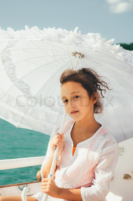 Stock image of 'girl sitting in a boat under a white lace umbrella hiding from the sun and looking at the camera'