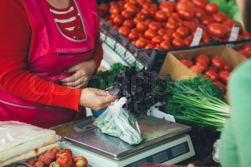 Stock image of 'the seller sells fresh Basil leaves on a summer day on the market'