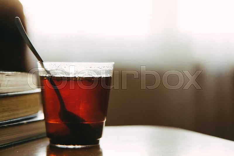 Stock image of 'Cup of tea in transparent glass with spoon and stack of books on table at workplace in the morning, selective focus, copy space'