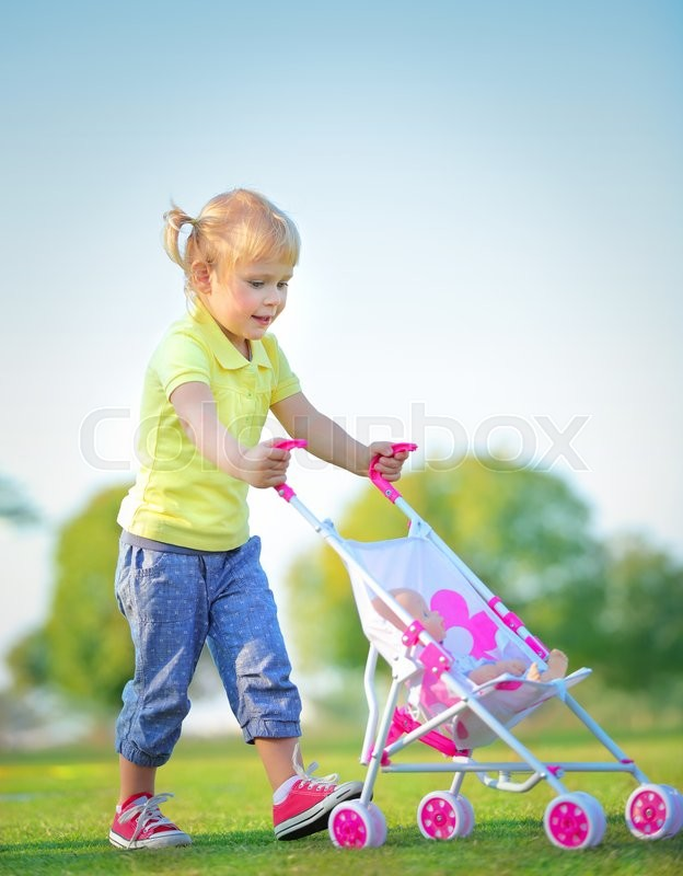 Stock image of 'Cute little baby girl walking with pram outdoors, happy child with toys playing in the park on a bright sunny day, preschoolers daycare\'