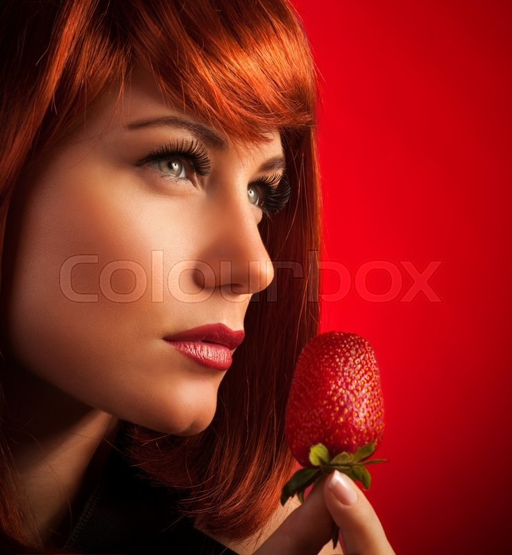 Stock image of 'Closeup portrait of a beautiful seductive female with fresh juicy strawberry, red background, enjoyment and temptation'