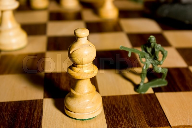 Stock image of 'Chess pieces and toy soldiers on a chessboard'