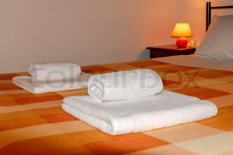 Stock image of 'Double bed with orange blankets.'