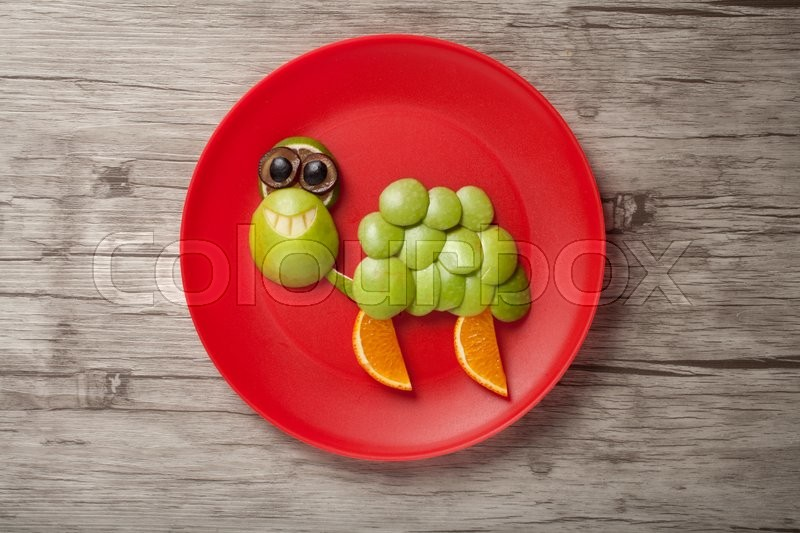 Stock image of 'Smiling turtle made of apple on board and plate'