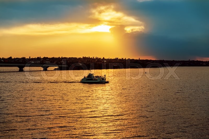 Stock image of 'Golden sunset in dramatic sky over river with boat'
