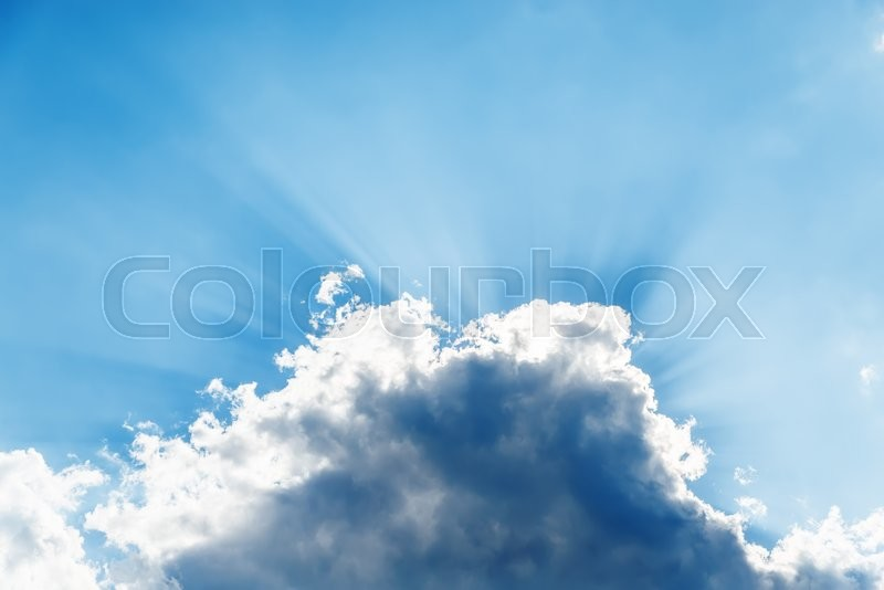 Stock image of 'Sunbeams over dramatic cloud in blue sky'