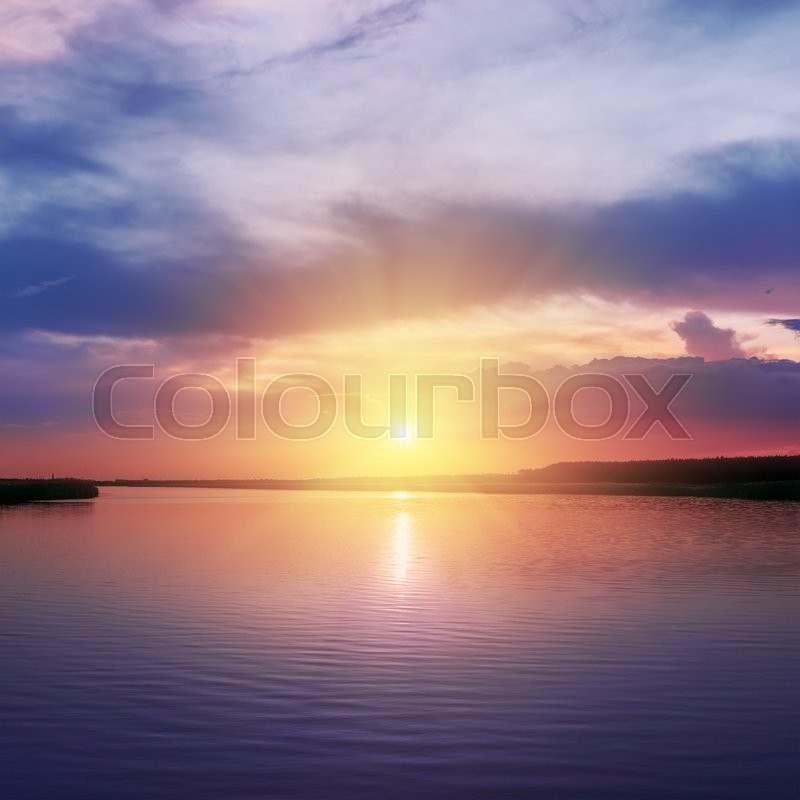 Stock image of 'Orange sunset over river in purple colors around'