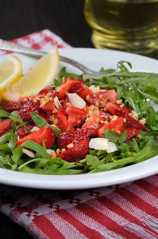 Stock image of 'Salad of arugula and strawberries with crushed peanuts, almonds'