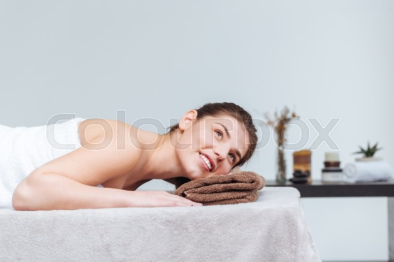 Stock image of 'Happy pretty young woman smiling and lying on massage table in spa salon'