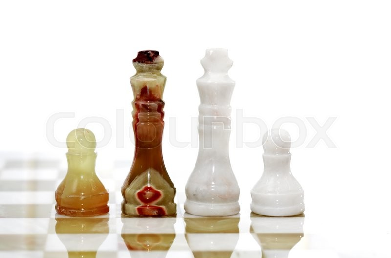 Stock image of 'Set of chess pieces made from Onyx on board against white background'