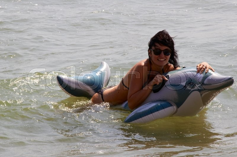 Stock image of 'Woman floating in the sea on an inflatable dolphin. a photo'