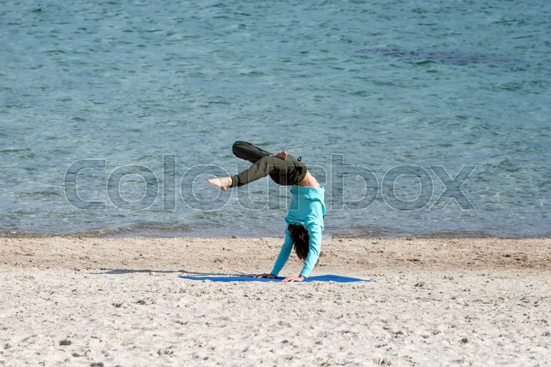 Stock image of 'Man doing yoga on the seashore. Young man exercising on the beach'
