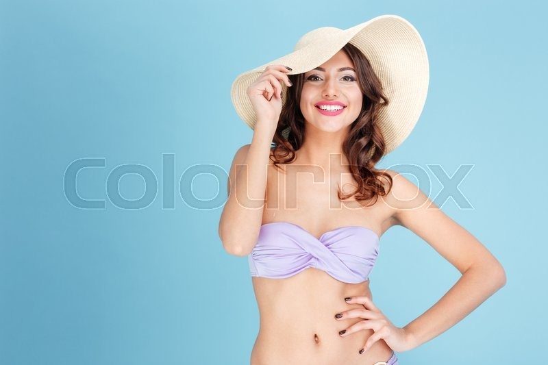 Stock image of 'Portrait of a smiling young girl in swimsuit and beach hat isolated on the blue background'