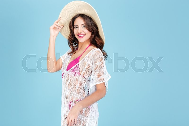 Stock image of 'Happy smiling brunette in bikini in a hat posing on blue background'